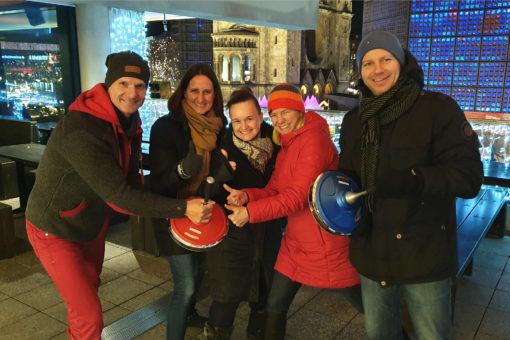 Das Team an den Eisstockbahnen mit der Gedächtniskirche und dem Kurfürstendamm im Hintergrund.